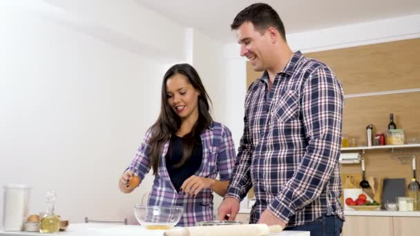 Woman in the kitchen breaks an egg while the man is bringing milk