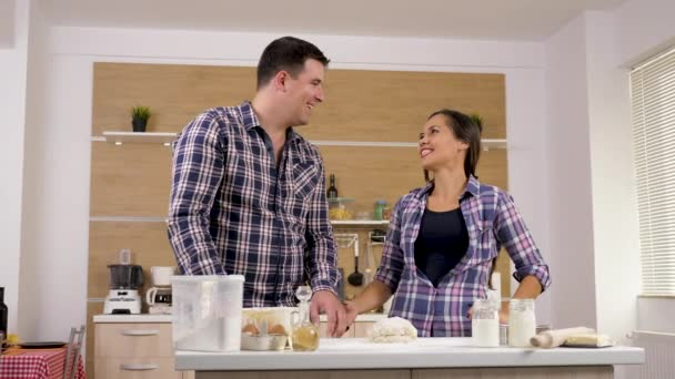 Happy couple in the kitchen playing with each other