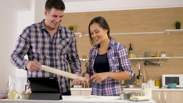Happy smiling couple cooking together in the kitchen
