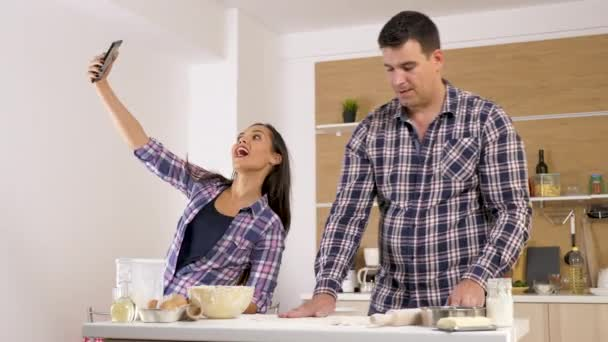 Woman taking selfie in the kitchen while the man is making food in background