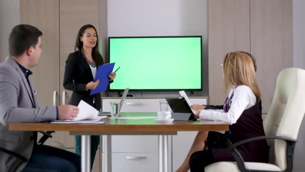 Businesswoman talking in the conference room in front of green screen TV
