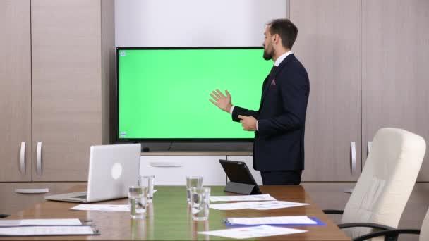 Kaufmann im Konferenzraum auf einem grünen Mock-up-TV-Bildschirm