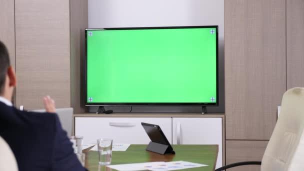 Geschäftsmann im Konferenzraum im Gespräch mit einem Greenscreen Mock-up Tv. Ersetzen Sie den grünen Bildschirm mit Ihrem eigenen Clip. Dolly Schieber 4k Filmmaterial
