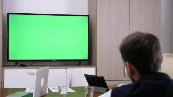 Unternehmer im Gespräch mit grünen Stuhl sitzen TV-Bildschirm