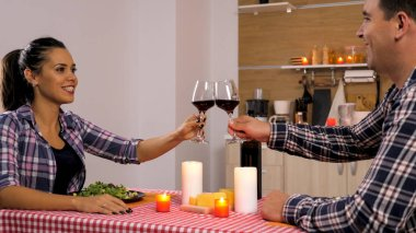 Happy young couple having romantic dinner at their new flat