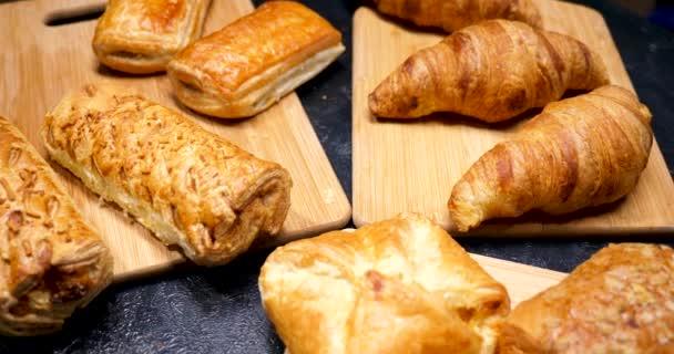 Čerstvé koláče, croissanty a dorty přehledně na dřevěných desek