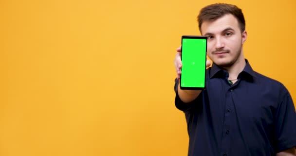Mladý muž drží v rukou telefon s zeleným plátnem
