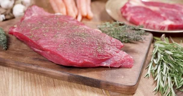 Čerstvé, syrové steak, dobře kořeněné na dřevěném prkénku s tymiánem a rozmarýnem