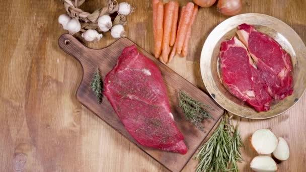 Rutschen und aufschlussreiche Aufnahme von rohem Fleisch auf hölzerner Oberfläche