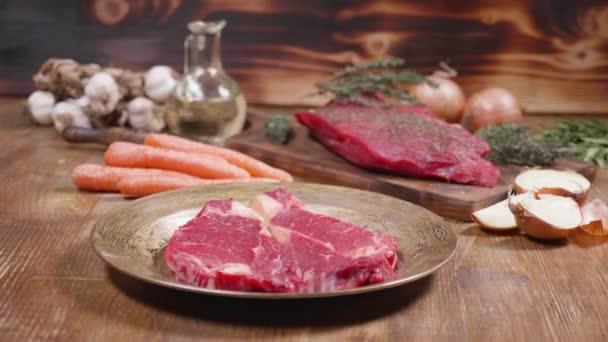 Pomalé slide hnutí ukazující dva kusy syrového masa a zeleniny na dřevěné pozadí