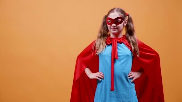 Fiatal lány öltözött öklét emeli fel szuperhős jelmez