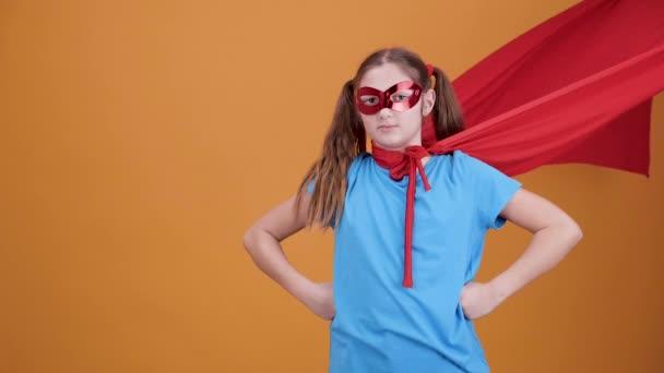 Ragazza giovane carina giocare super eroe su una priorità bassa arancione della priorità bassa