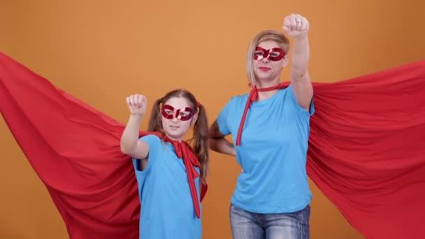 Egy fiatal lány és egy nő, mint egy narancssárga háttér előtt szuperhősök