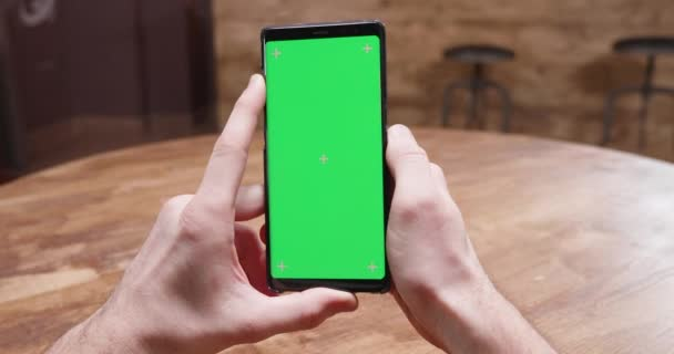 POV shot of male hands holding a phone with green screen