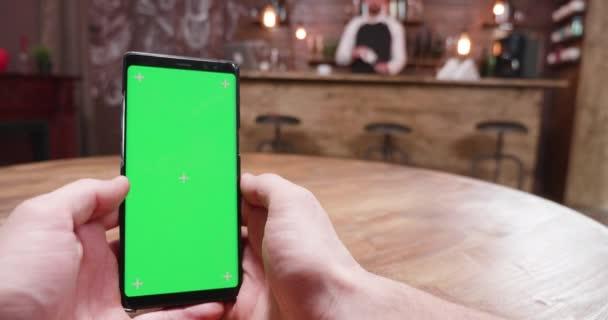 Kézi lövés az ember egy zöld képernyő smartphone egy vintage pub