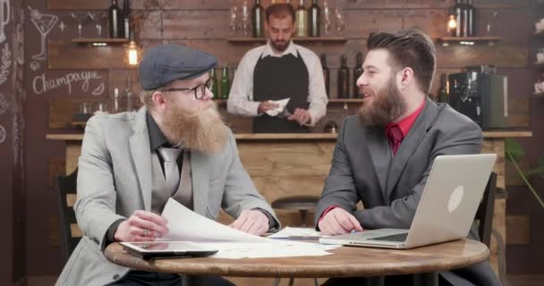 Young handsome bearded freelancers have a chat at a informal business meeting