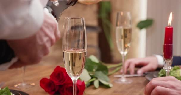 Champagner in einem Glas auf einen Tisch mit Kerzen und roten Rosen gießen