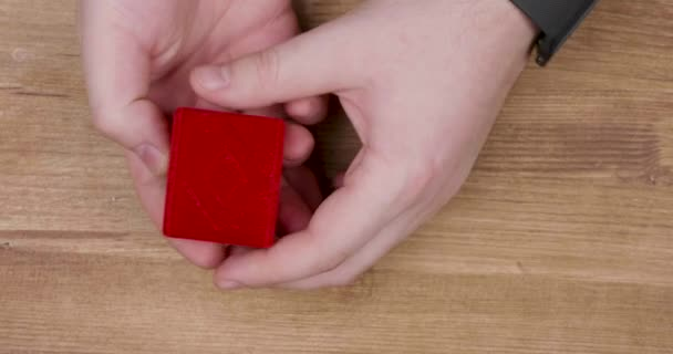 Man hand opening a small red box with engagement diamond ring