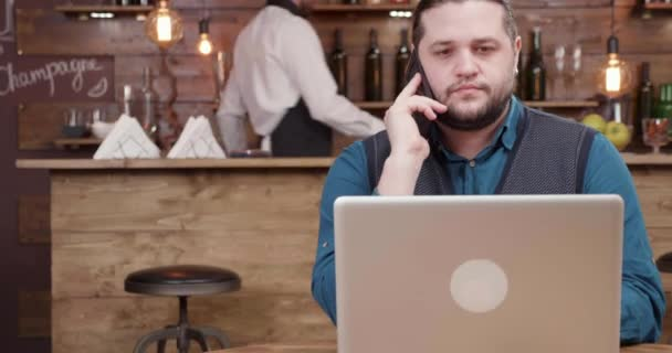 Ambitious young entrepreneur making a phone call while in a cafe