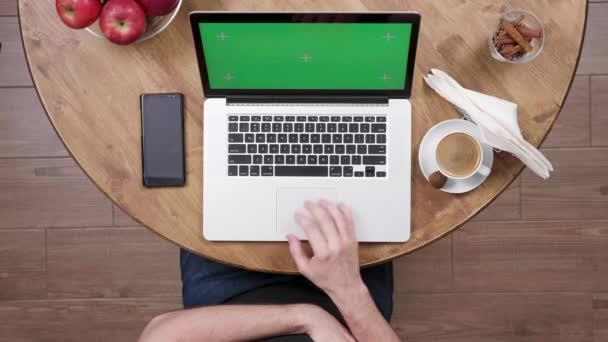 Fiatal ember segítségével a touchpad, és nézi a zöld képernyő a laptop