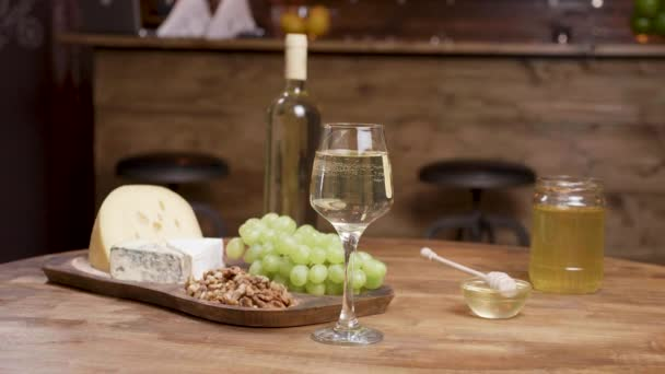 A bottle and a glass of wine combined with cheeses