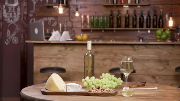 Paralaxy záběr řadu sýrů podávaný s bílým vínem