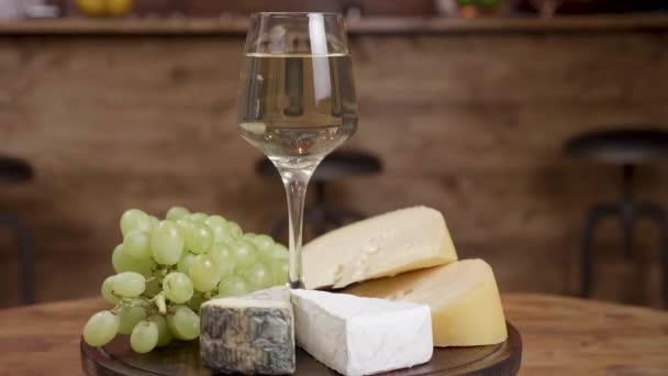 Krásný rotace sklenku vína s variací sýrů na kulatý Dřevěný tác