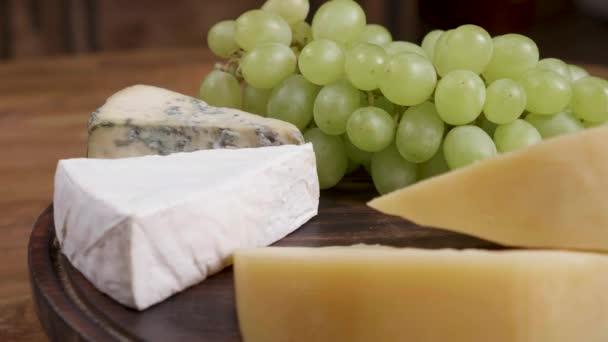 Gouda, brie a dorblu sýr podávaný s bílými hrozny