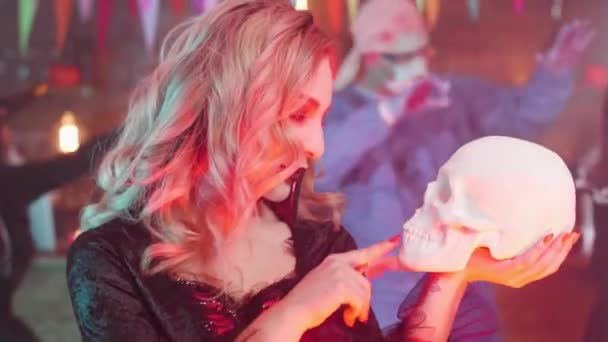 Beautiful woman in a vampire halloween costume with a skull in her hands
