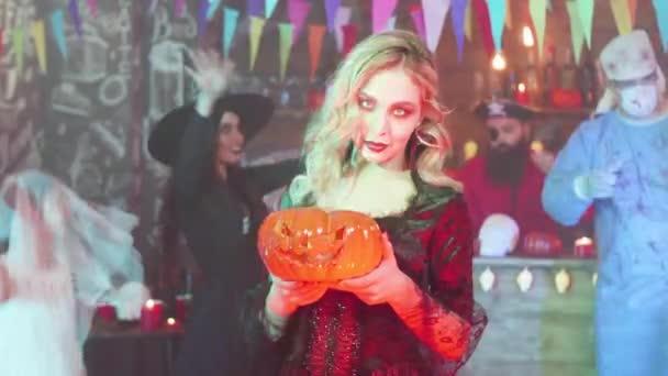 Sexy Vampire mit einer Jack-o-Laterne in den Händen auf einer Halloween-Party