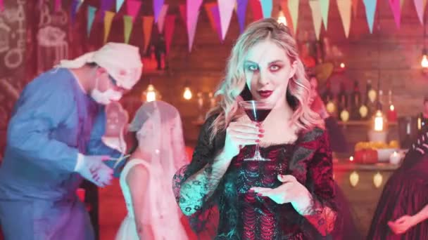 Young woman dressed in a vampire costume drinks blood at a halloween party