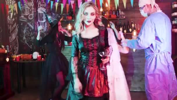 Sexy Hexe hält ein Glas Blut in ihren Händen und tanzt langsam auf einer Halloween-Party