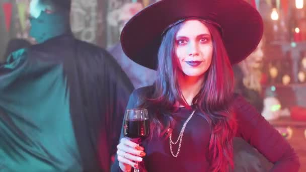Woman dressed in evil witch costume drinks blood from a glass