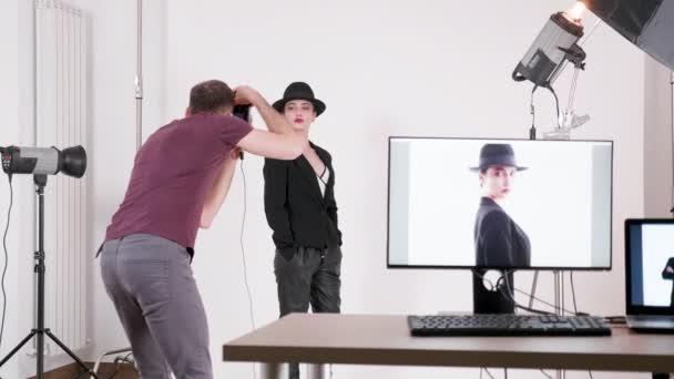 Modella professionista che indossa un cappello e fotografo che scatta foto di lei