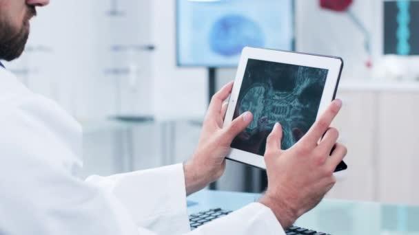Arzt sucht und analysiert Röntgenbild auf einem digitalen Tablet-PC-Bildschirm