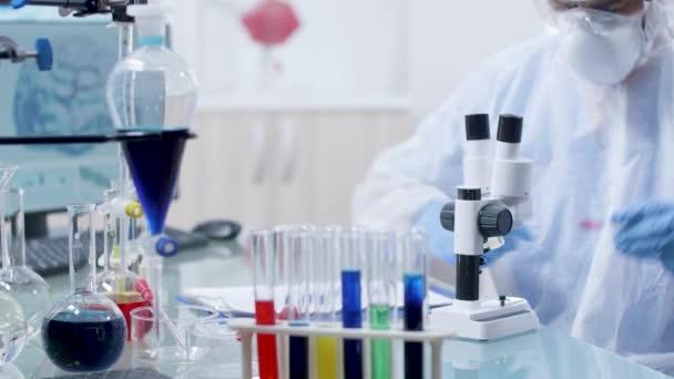Tudós nézi minta a Mikroszkóp alatt, majd úgy jegyzetek