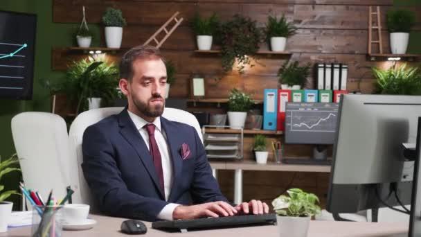 Přiblížit záběry pohledného chlapa v obleku, který pracuje sám v kanceláři