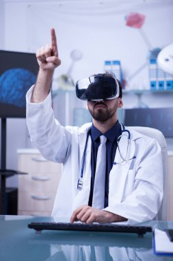 Young male doctor with virtual reality headset pointing
