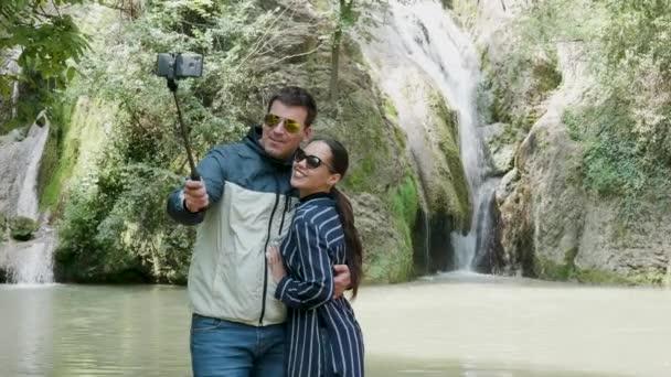 Gorgeous tourist couple takes a selfie near a waterfall