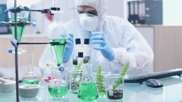 Közelkép a biotechnológus íróasztaltól, kémcsövekkel és mintákkal