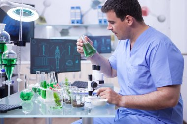 Side view of young scientific man holding a green solution in his research lab