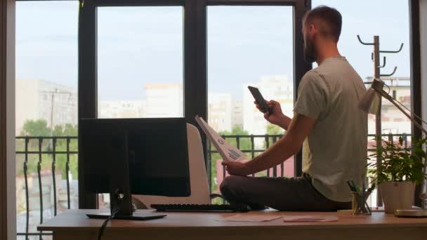 Samotný podnikatel v kanceláři, který se dívá na mapy a grafy v teplém slunci