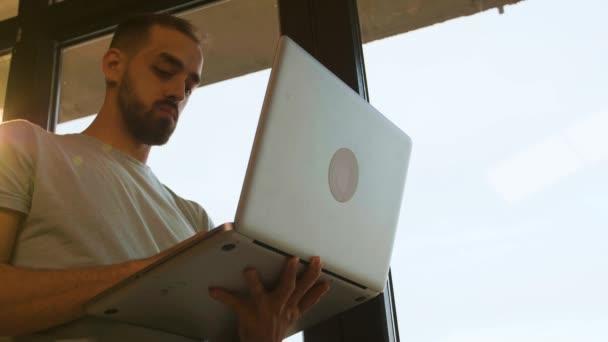 Nízká úhlová střela manažera pracující na přenosném počítači v blízkosti okna