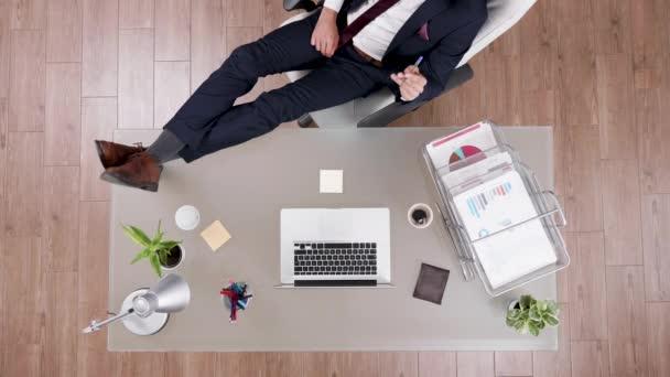 Nejlepší pohled na obchodníka v obleku, který zůstal uvolněný nohama na psacím stole