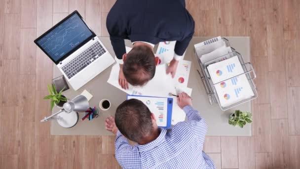 Blick von oben auf den Geschäftsmann in seinem Büro, der verschiedene Diagramme analysiert
