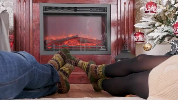 Man and woman feet in front of the fireplace next to a Christmas decorated tree