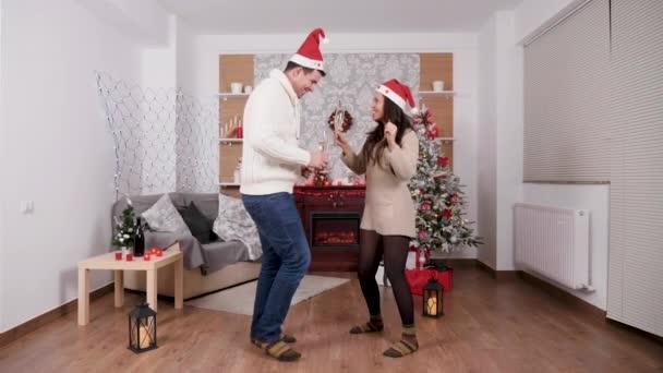 schönes glückliches Paar mit Champagnergläsern in den Händen, die an Heiligabend tanzen und Spaß haben