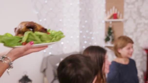 Shromáždění velké rodiny kolem vánočního stolu s vánočním stromku na pozadí