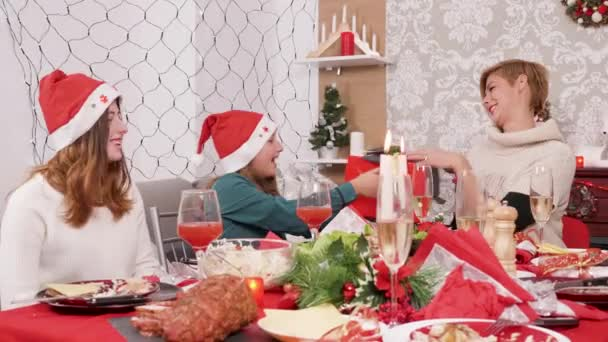 Smiling mother at christmas feast gives her daughter a gift box