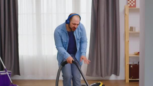 Muž se sluchátky během úklidu